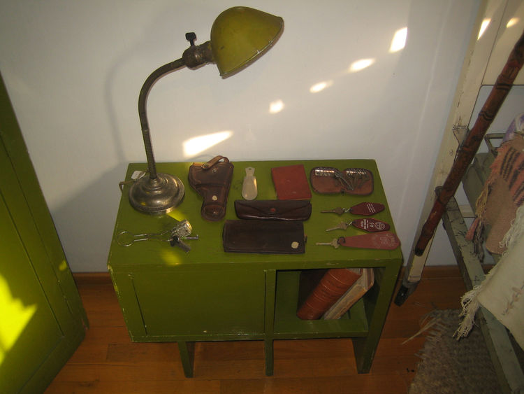 This little side table was next to a small bed. It has all manner of cases and keys on it including a holster for a pistol.