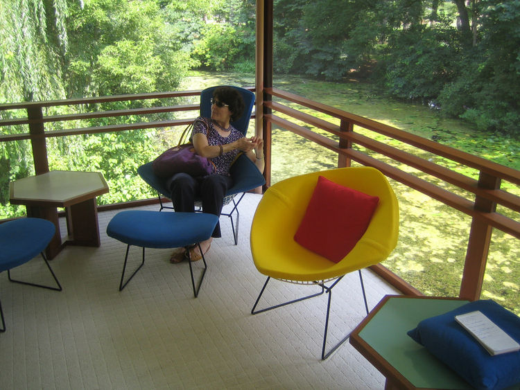 This screened-in porch is on the second level of the house and overlooks the big pond. I love the colorful Bertoia furniture. The end tables were done by Dow himself.