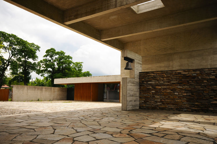 Another view of the central courtyard with the waiting room in the distance. The architects chose to leave their materials—Cor-Ten steel, oak, concrete and stone—solid and untreated, allowing for the natural process of aging to be symbolic of the cycle of