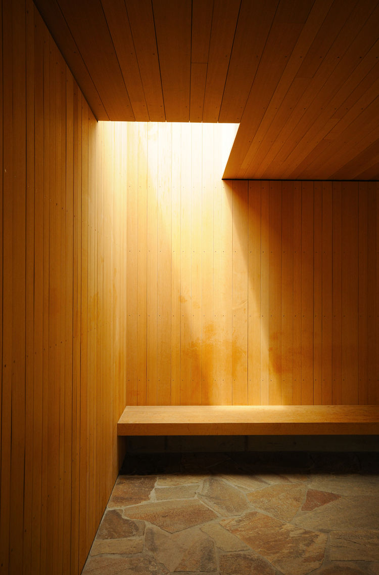 A constantly moving shaft of natural light that edges along an oak bench is a defining element in the room.