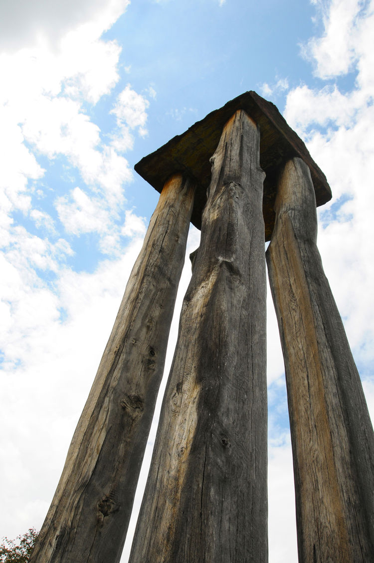 The towering sculpture of natural, untreated wood rises far above the pathway.