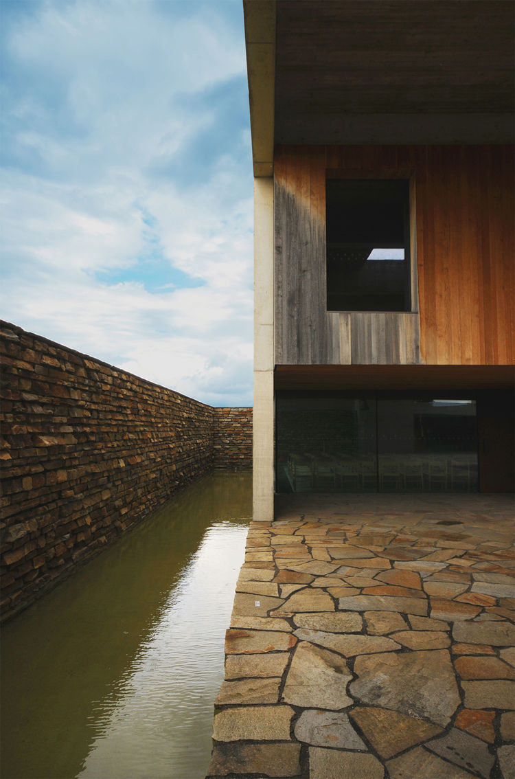"Protected by a natural stone roof, the mortuary's upper half comprises a smooth oak cube contrasted with the quarried stone surrounding walls and floor. The architects conceived the water feature as a ""golden water surface [that serves as] a meditative fo"