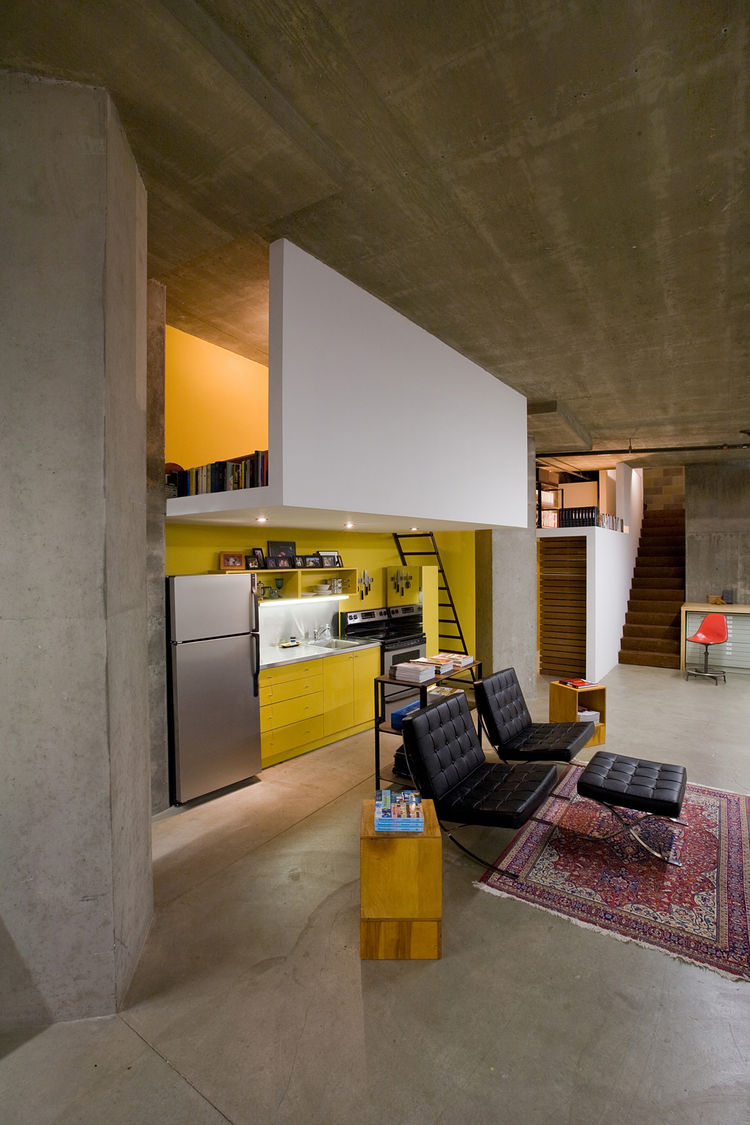 """The kitchen didn't really have a home,"" says Colkitt. His solution was to build the sleeping loft directly above it, giving the kitchen some architectural congruity, and implement recessed lighting into the dropped ceiling, also the underside of the floo"