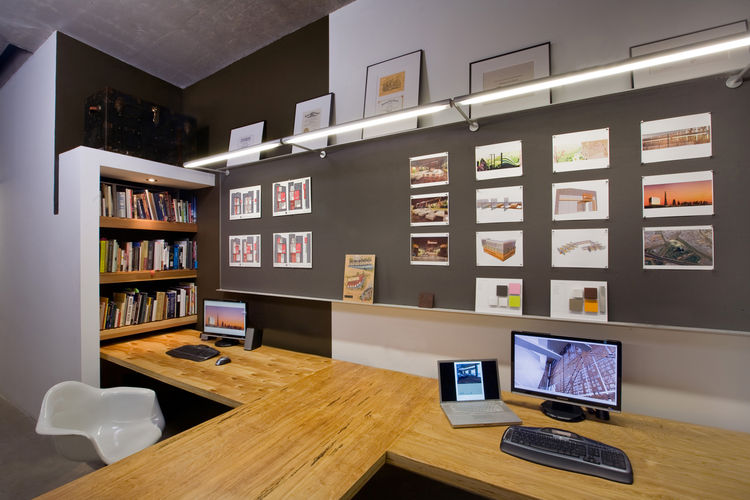 "Colkitt built the plywood desks and implemented bookshelf to temper the awkwardness of the wall jutting out behind it. More Homasote work boards are illuminated by fluorescent lighting. Photo by <a href=""http://www.ramsayphotography.com/"">Cheryl Ramsay</a"