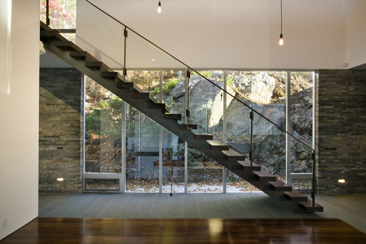 "The first floor of the Artreehoose by <a href=""http://www.d-bd.com/"">Della Valle Bernheimer</a> in New Fairfield, Connecticut, is completely wrapped in glass. One side overlooks Candlewood Lake and the other (shown here) butts up against a large boulder."