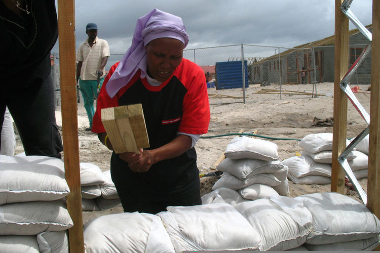 Once the frame of the house was constructed, the townspeople filled the wall space with sandbags. Here, Olga Jonkers uses a handmade tool to compact the bags that will become the walls of her future home. Image courtesy <a href=http://www.interactiveafric