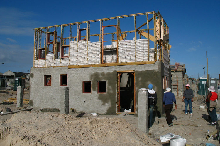 "The plastered-wire-mesh finish gives the homes the look of a house constructed of bricks or concrete, ""like any other building,"" Mpahlwa says. In this photo, the frames for the second floor have been erected and are partially filled with sandbags. Once co"