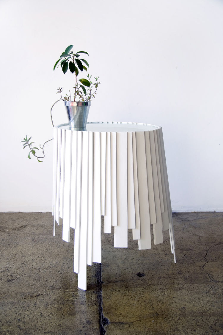 The Matryoshka series is defined by overlapping wooden slats, as though paint had dripped down the side of this end table, drying in rectangular globs.