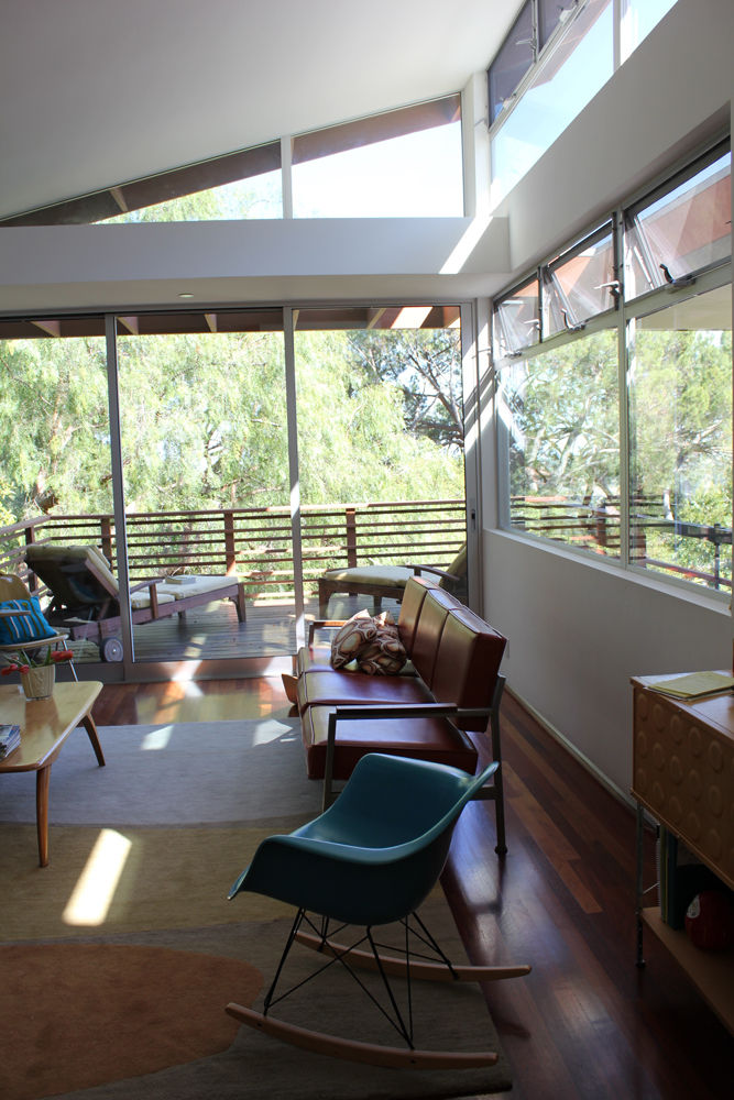 The main living room area is filled with light from the South and East, overlooking a valley of Mount Washington towards Montecito Heights. The teal rocker and storage unit at right are Eames designs, the leather sofa was salvaged from a public school, th