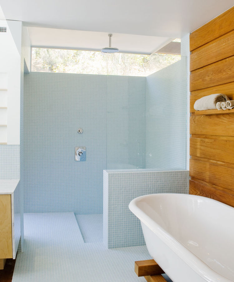The clerestory makes for a bright master bath, with soothing blue glass tiles by Hakatai cover walls and floor alike. Appealing contrast of textures and light might be why this design team have completed sixteen projects in the area, half new built, half