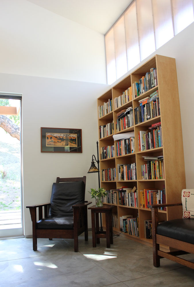 "Current owners melded their former dwelling's period furnishings—an L. & J.G. Stickley settee at right, William Morris attributed chair, and Handel lamp—with their new setting.  The reading area is ""an homage to our craftsman home we left to live here,"" s"