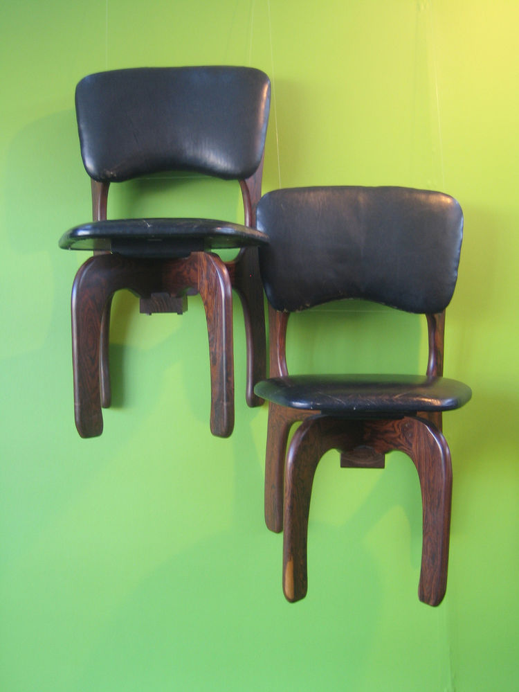 Don Shoemaker's 1960s rosewood chairs from Mexico aren't too functional suspended on the wall, but they look beautiful against a lime green background. -Sarah