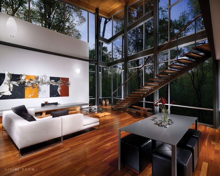 The entrance progresses from the top of the hill, across a bridge and into a balcony foyer. There the forest fills the interior through north-facing glass walls. A stair descends past the glass to the main living floor, which opens onto a partially seclud