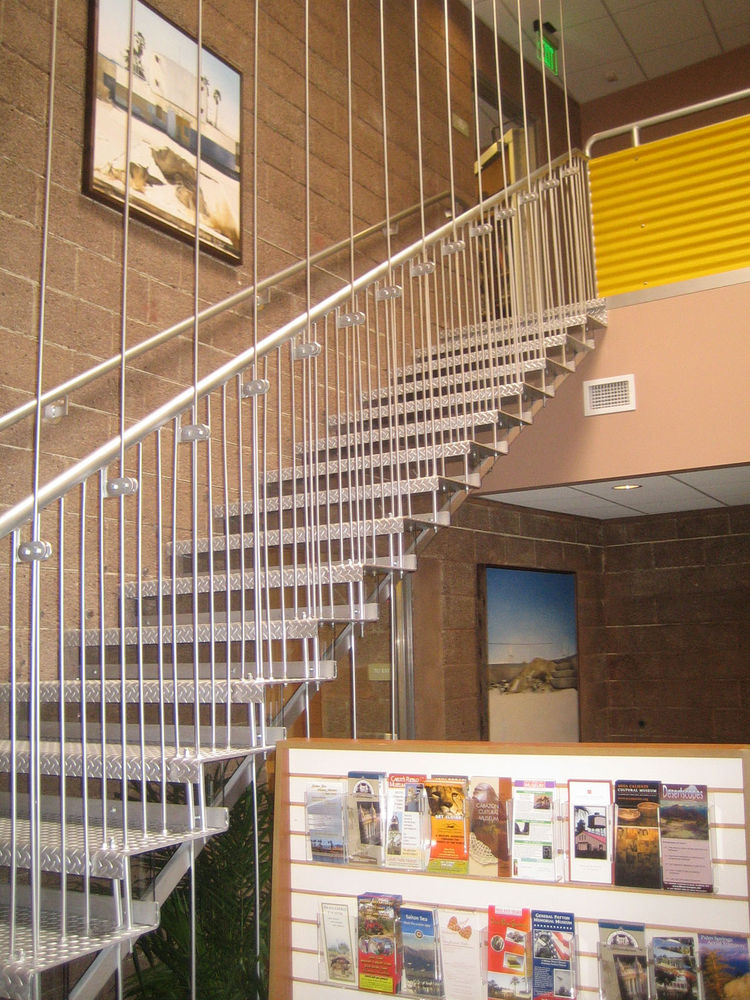 Finally, here's a glimpse of the wonderful modernist staircase you see when you come in the front door. It's certainly the boldest architectural move on the interior, and when paired with the cinder block walls, it immediately evokes its era. Kelly told m