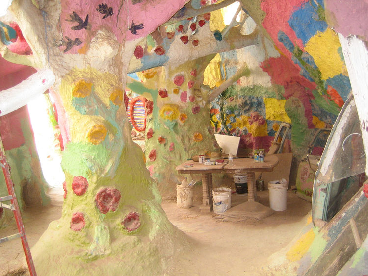 "This pastel room made of ""trees"" cobbled together from tires, beams, branches, and the like is still under construction. It also felt like I'd wandered into some Candyland version of the desert."