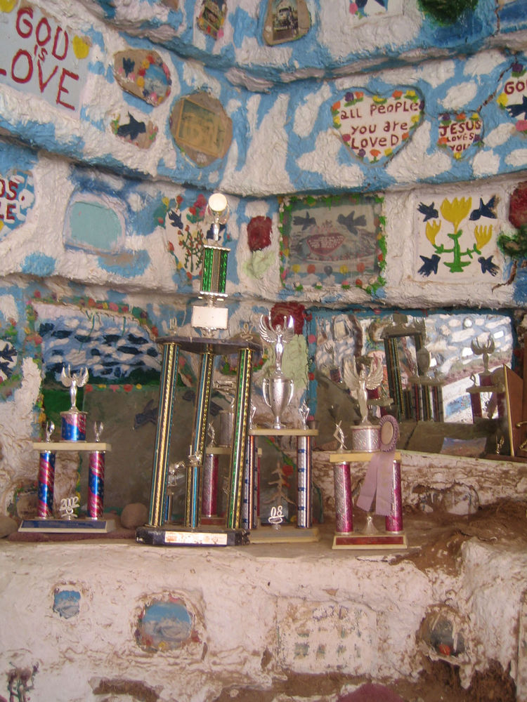 "Here's one of the rooms inside the ""Museum."" It's really colorful and covered in the same kind of Christian messages as the rest of the place. The group of trophies was surprising, however. Some of them are prizes from a local tomato competition."