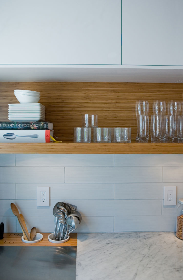 Davison covered the countertops with stainless steel (chosen for its thinness) and inset a piece of carrera marble for baking preparations. Wittenborn, the contractor, cut two circles in the bamboo counter section to fit utensil cups, replicating a detail