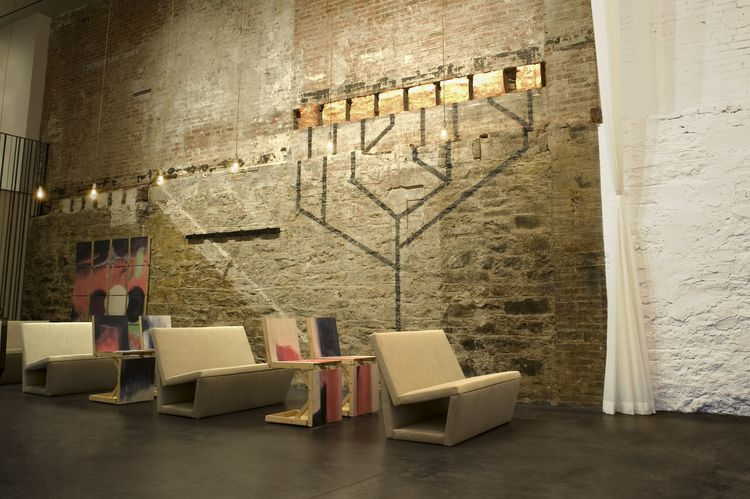 Along one wall is a towering menorah fresco, created with black painted lines and seven glowing square bricks that were found in the foundation during the renovation. Here you can see the convertible chairs plucked from the wall and set up to seat additio