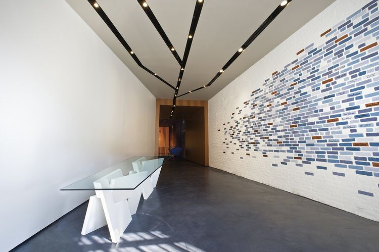 The first thing you see when you enter the synagogue is a long narrowing reception area. The sculptural reception desk is made of two white QuaDror feet and a transparent glass top. A donor wall with blue bricks acknowledges financial contributions. Conve