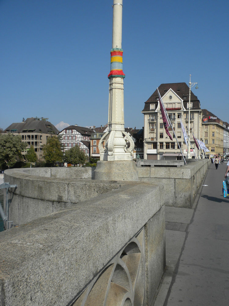 I'd seen images of urban knitting and knit graffiti all over the web but had never seen it in person before I visited Basel. Each light post along the Mittlere Brücke was decorated with its own knitted sleeve like the one in this image.