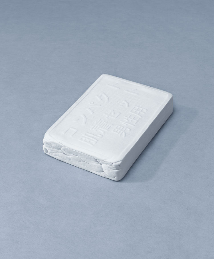"""When soaked in water, this 13cm x 8cm brick of """"compressed clothing"""" from Japan expands to become a t-shirt, pants, pair of socks, and a towel. Photo: © Usefulness in Small Things, Rizzoli, 2011."""