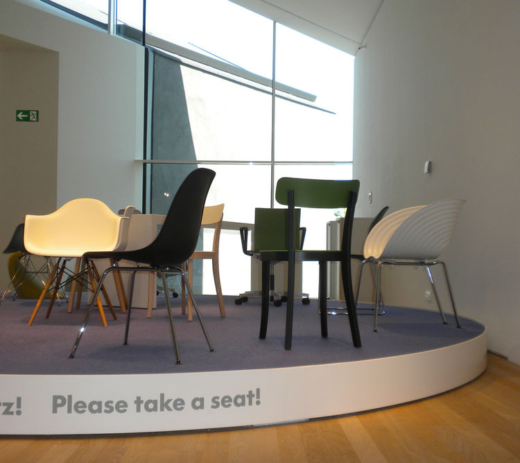 One of the best things about the VitraHaus is that you're encouraged to get a real feel for all the furniture by taking a seat, as this sign recommends. On display here (left to right): a white Eames Plastic Armchair DAW by Charles and Ray Eames, a black