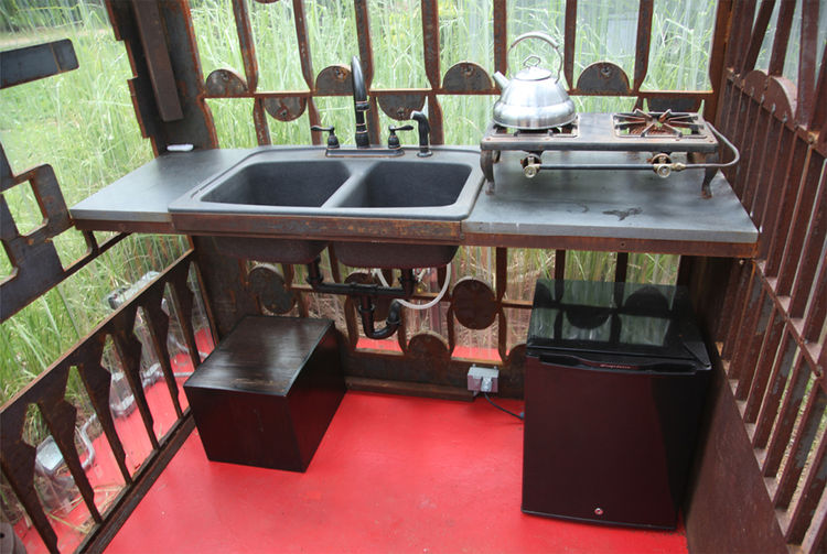 """Inside the small space are a sink, propane stove, and small refrigerator. """"The kitchen only needs to function for one or two people so the six-by-six footprint is satisfactory,"""" Sewell says."""