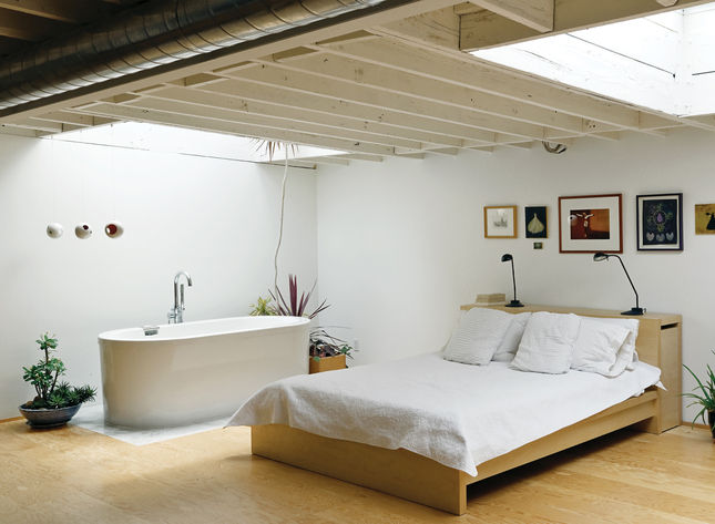 Upstairs is a serene bedroom with skylights, exposed rafters, and an a bathtub open to the rest of the room.