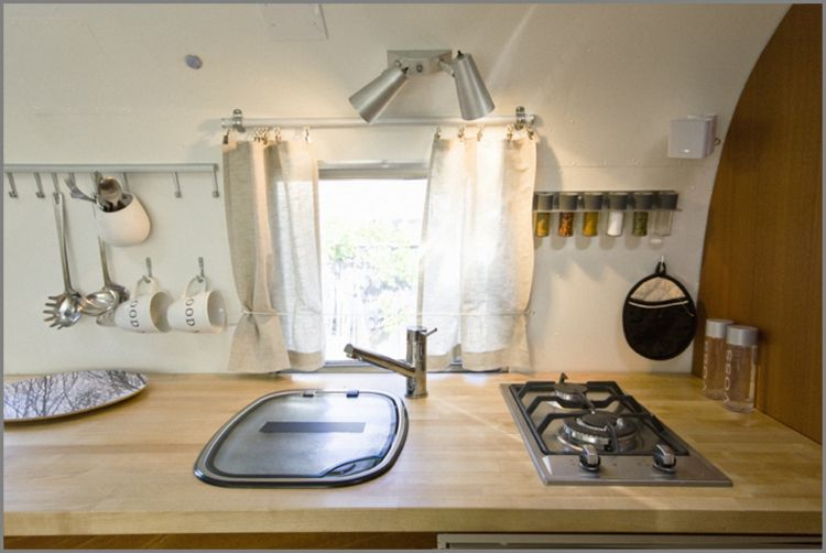 The countertop is from Ikea, the camping sink is by Thetford, and the stove is by Ramblewood.