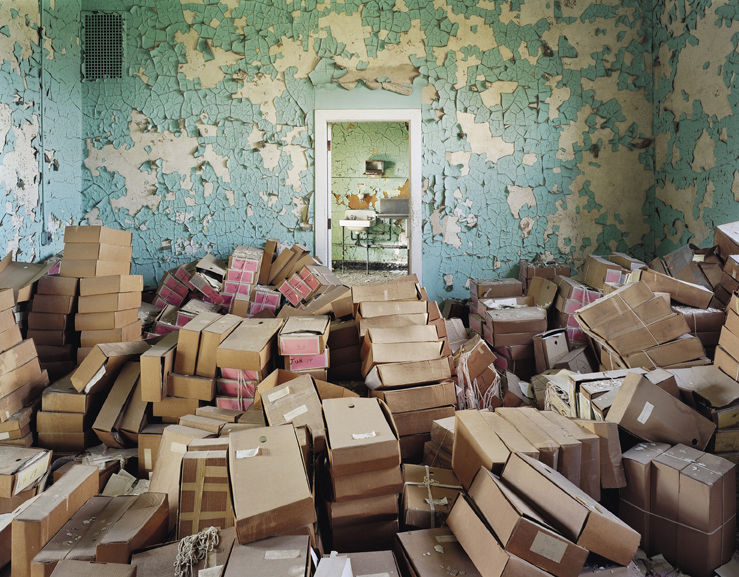 Crumbling paint serves as a proper backdrop to these boxes of files and state records at Spring Grove State Hospital in Cantonsville, Maryland.