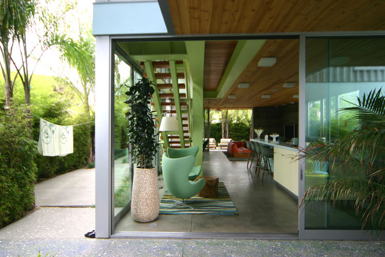 """""""They asked that the house be able to be hosed out. They are avid surfers so there is an outdoor shower and surfboard rack; in fact the only bathroom downstairs is outdoors. This kitchen is also part of the main space of the house and is central to family"""