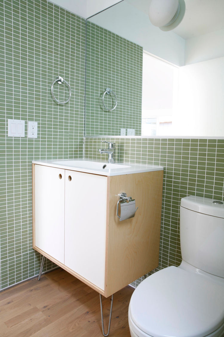 """In the bathrooms, Sweet used a mirror to enlarge the feel of the space. They kept the costs minimal by using Grohe bath fixtures and an Ikea sink.<br /><br /><p><em><strong>Don't miss a word of Dwell! Download our </strong></em><a href=""""http://itunes.appl"""