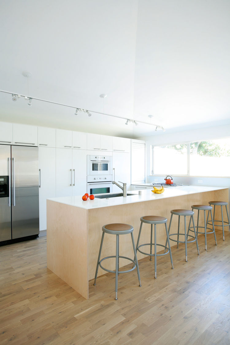 Sweet kept the kitchen renovation within budget by mixing Ikea cabinetry with custom plywood touches. The money they saved went into a nicer countertop and sink. He also maintained the home's informal feel (and saved space) by using the bar area for infor