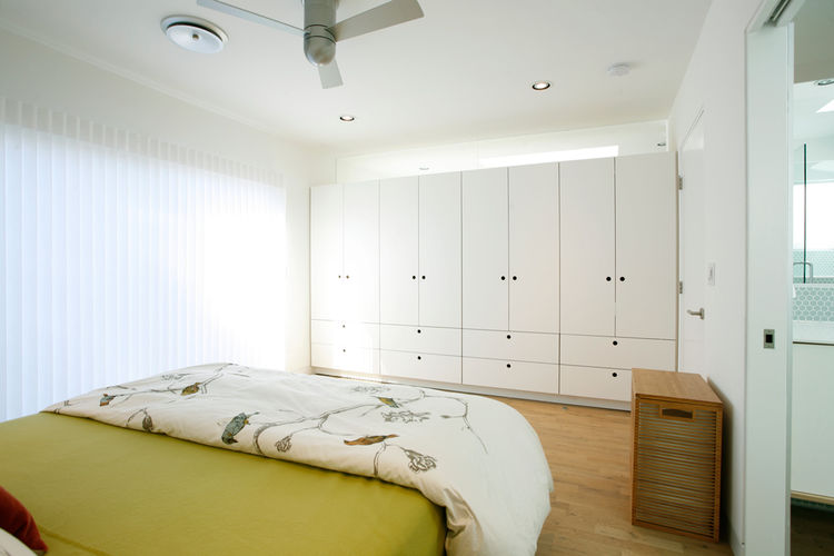 In the master bedroom, Sweet installed a row of custom cabinets that take the place of a wall. While acting as a barrier between the bedroom and the hallway outside, the cabinets also stopped a few inches below the ceiling so as not to completely block of