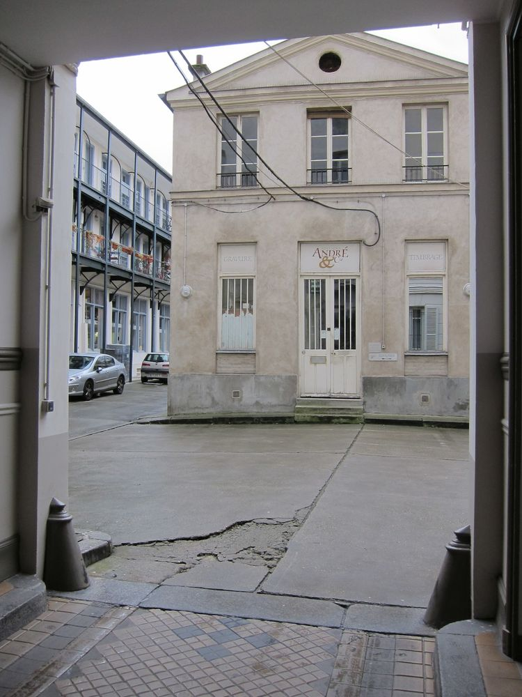 Entering off the street, you walk through a covered area and enter a large courtyard lined with three-story industrial buildings. A freestanding building in the center of the courtyard houses a printing press.