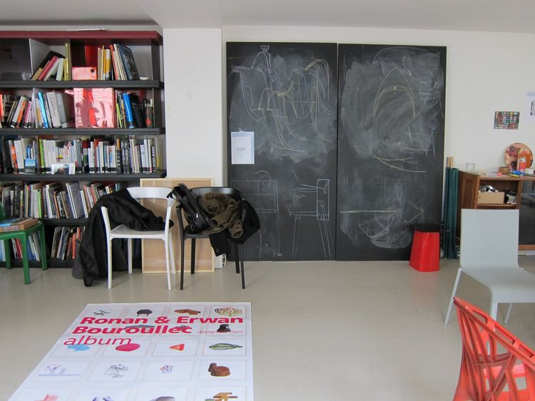 """Inside, the main floor of the studio is pleasantly cluttered with books, sketches, chair prototypes, finished products, and a blackboard where the brothers hash out their ideas. On the floor is a poster for their """"Album"""" exhibition in Bordeaux. Downstairs"""