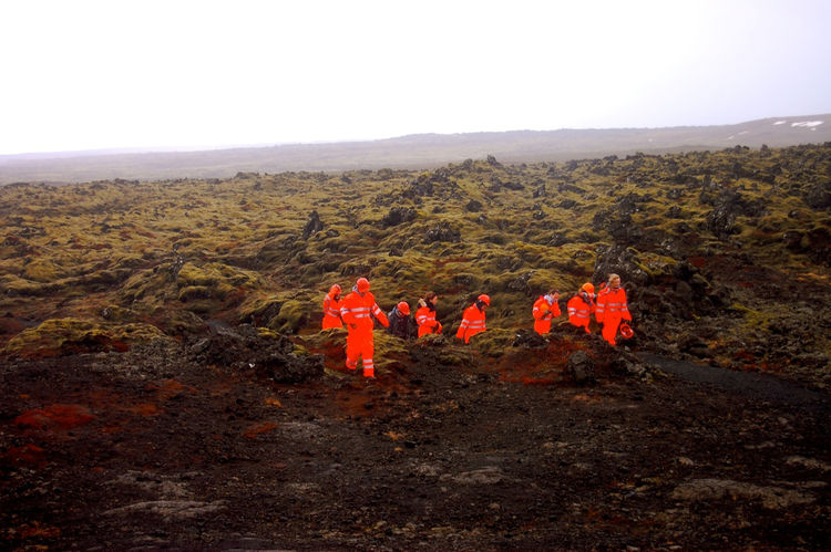 While driving through a field of moss-covered volcanic rock, I spotted a group of cave explorers in orange, reminding me of a team of astronauts walking on another planet.