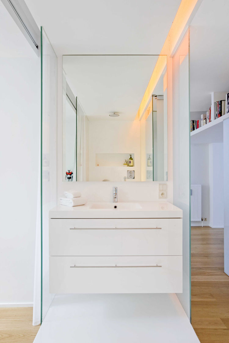 In an unconventional twist, the bathroom is separated into two rooms: a glass-walled shower/sink area shown here and a more private room for the toilet.