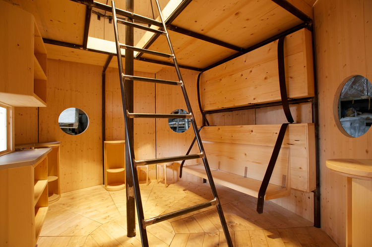 The two-story structure's interior is clad in pine. On the ground floor, two single beds are held in place with leather straps and can fold down for seating during the day. There are two double beds on the mezzanine level. Perriand, an avid Alpine mountai