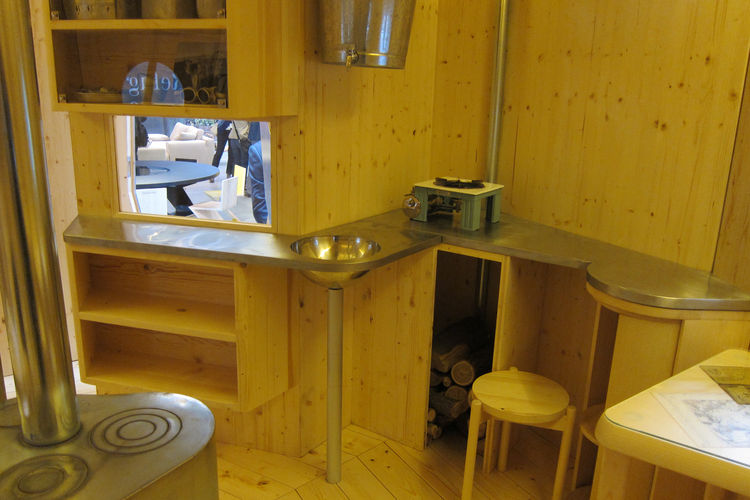 "The ""kitchen"" is comprised of a stainless-steel worktop, a steel basin for melting snow, containers for staples, and a shelf for a camping stove."