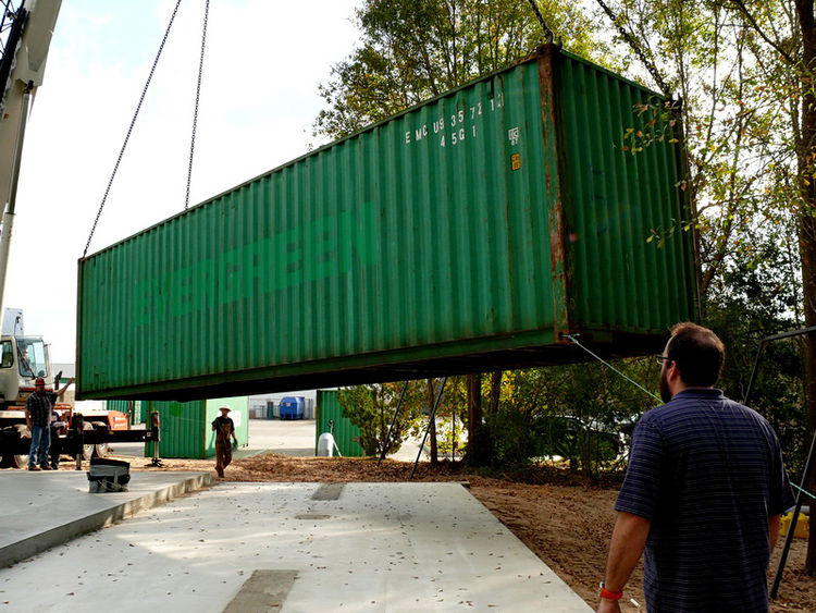 "After the foundation is set, the containers are moved into place. ""I don't want a building like everyone else's. I want one that gets you excited about coming to work in the morning so we turned to cargo containers and that got the juices flowing,"" says C"