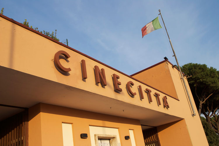 "Architect Gino Peressutti designed Cinecittà circa 1935, in the ""Italian Rationalist"" style, seen here in the bold lines and sans serif font of the front gate.  Unlike the earlier Italian avant-garde, Rationalists didn't want to rip apart traditional arch"