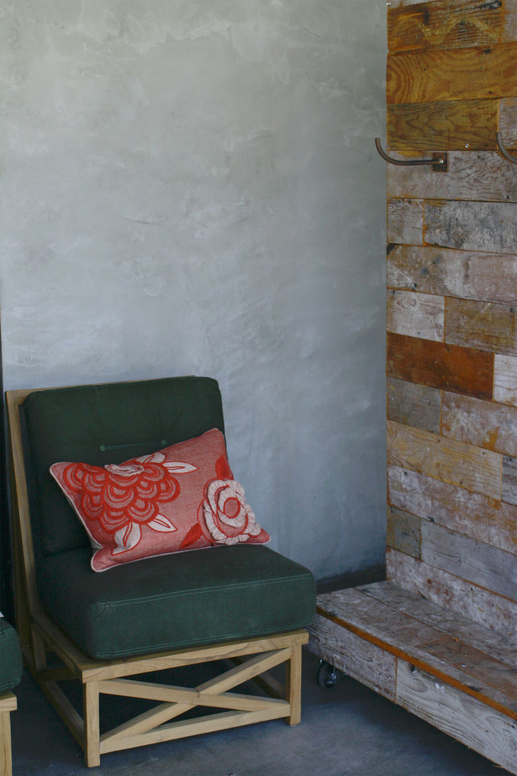A teak outdoor chair upholstered in old army tent canvas.