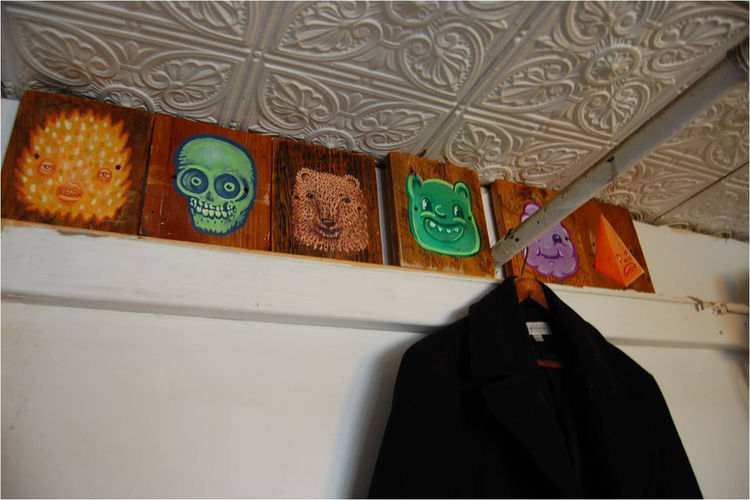 Faces on wood blocks line the ceiling.