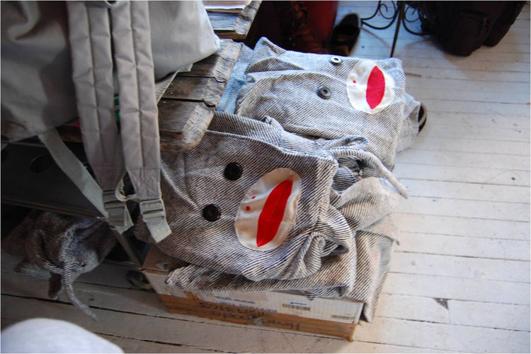 "<a href=""http://headhoods.com/"">HeadHoods'</a> sock monkey designs are stacked neatly on the floor."