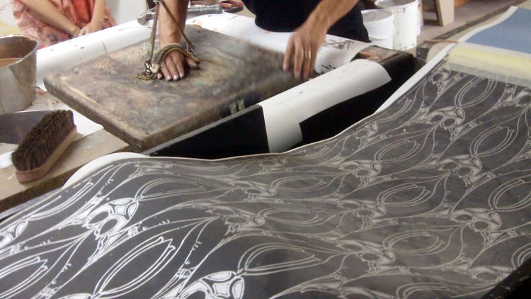 During block printing, color is applied under the pattern. The carved wooden block patterns are inked by pitching and rolling them against a thick wool-felt pad and then pressed (using pressure from both the hand and foot, by standing on a wooden pedal) a