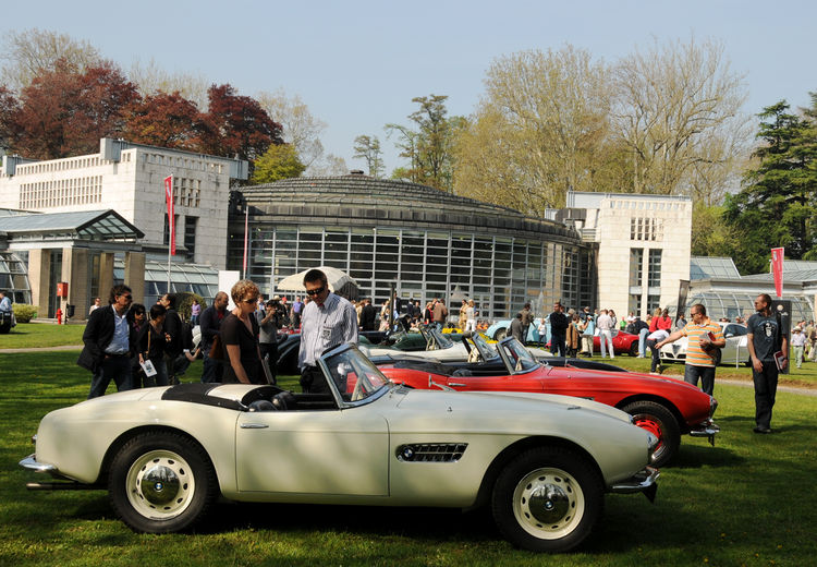 A look at Bellini's dome with a collection of rare BMW 507s and visitors at Concorso d'Eleganza. According to Bellin's design notes, the walls are built with cement blocks with rose-ochre paste coloring, echoing that of the front of the existing Villa Erb