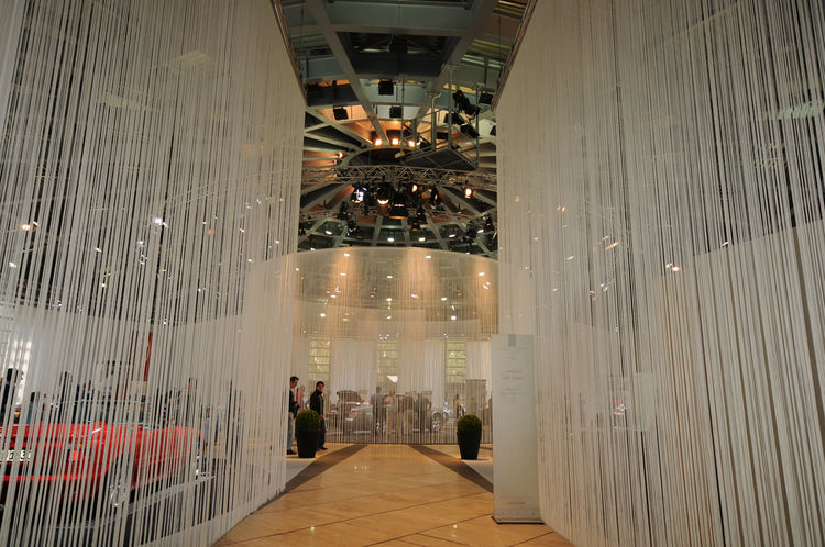 Exhibition designers choose simple fabric strings to create and separate space for this exhibit, which minimizes waste after tear-down and allows both natural and artificial light to filter freely.