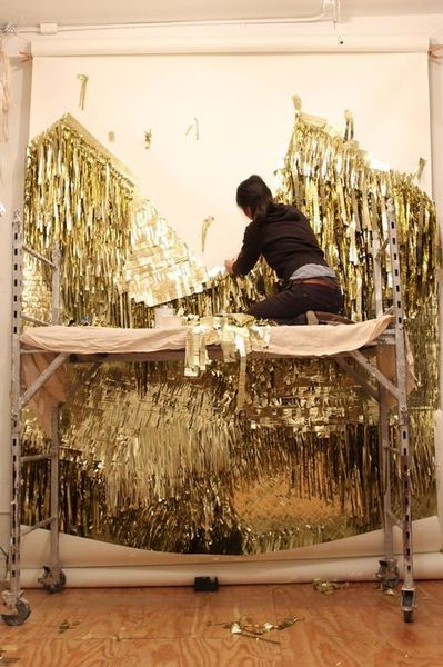Ho at work on a golden wall installation.