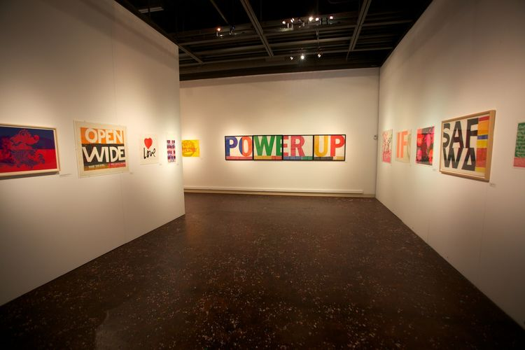 """Here's a view of the gallery, with Corita's iconic 1965 """"Power Up"""" piece in the background."""